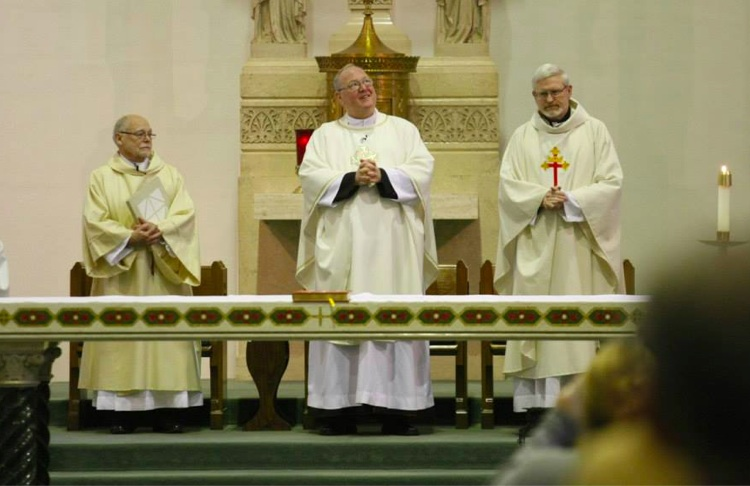Cardinal Dolan is flanked by Deacon Clyde McEntire (left) and Father James Gray at the beginning of the service.