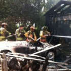 Firefighters dowse a garage fire in Webster Groves. A vintage MG was severely damaged.