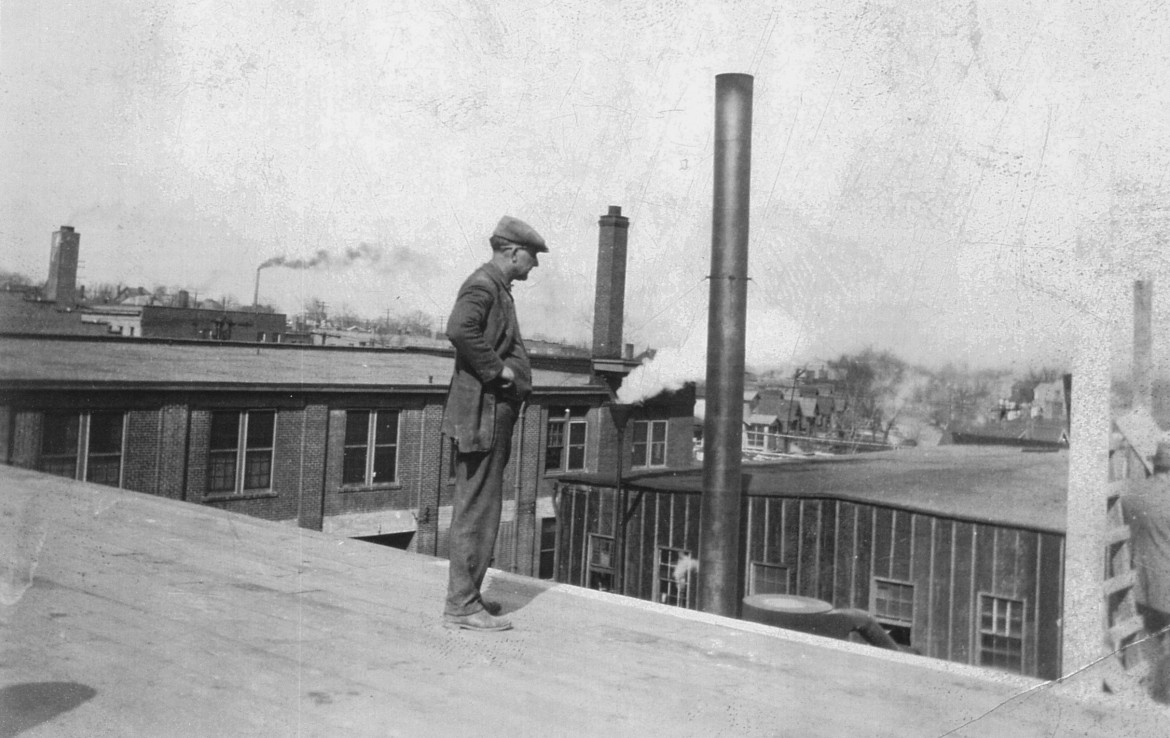An unidentified man standing on the roof of the current mill building.  he is apparently looking at the scaffolding being used to construct the chimney which was thoughtfully saved during restoration.  the original tar paper covered mill building can still be seen as can the Saratoga Lanes building.