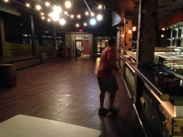 Andrew Graefe pulls birch bark panels off the bar Wednesday evening at the future Jukebox Piano Bar.