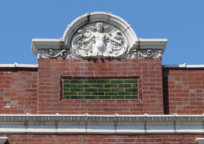 This atop the parapet of our first City Hall building on Sutton. the baby has wings so it must be a cherub, I suppose. I haven't the faintest idea what an ornament like this could signify. cherubs have been around at least since the baroque period (look it up. I can't do everything for you).