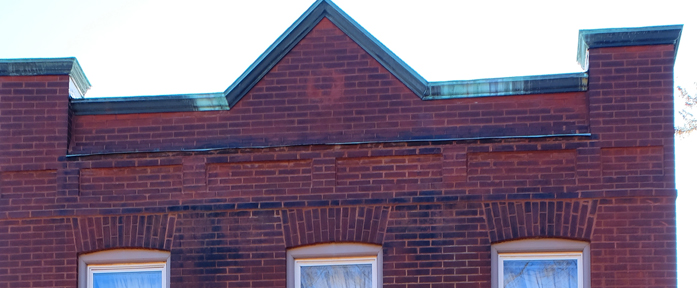 facade which faces Sotuh Street on the north has some nice robust brick arches over the windows. It even still has wht I would guess might be an original copper cap on the parapet. Look closely and you can see a ghost of something circular that was once hanging in the center.